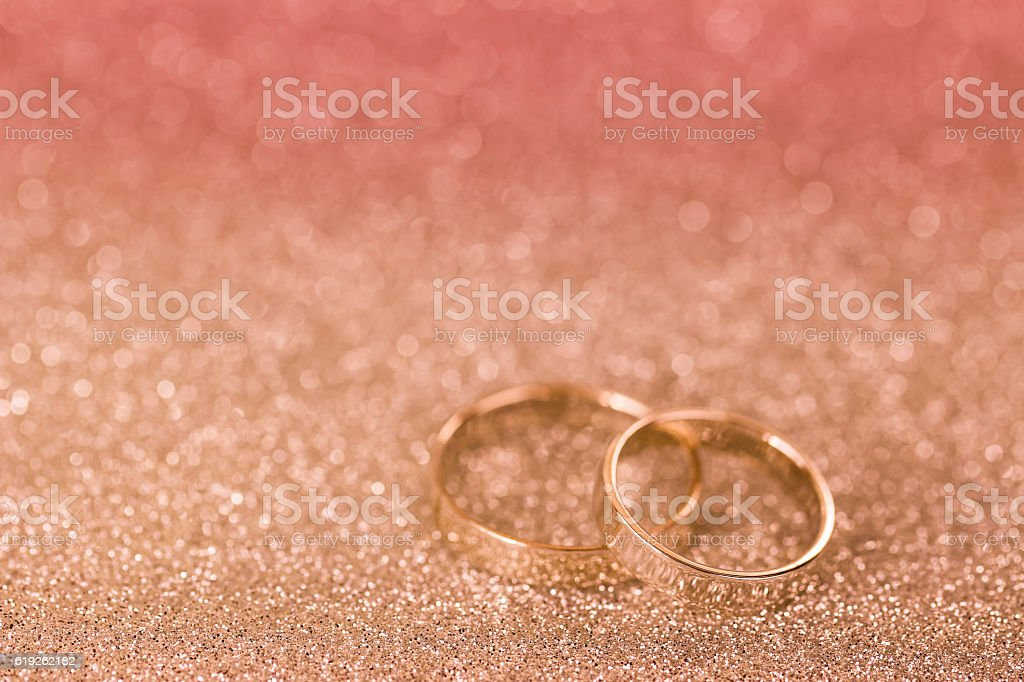 Silver rings on glittery background with pink filter and copyspace stock photo