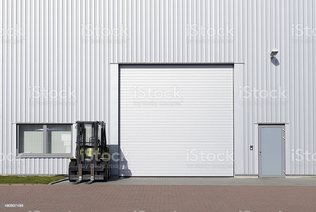 Silver rolling garage door and forklift stock photo
