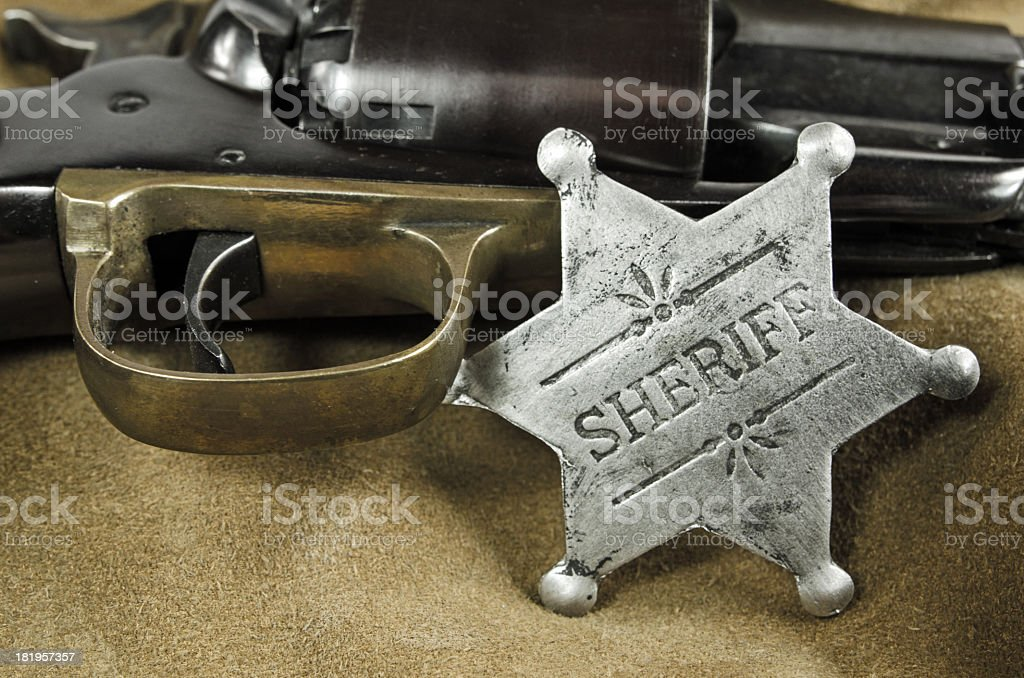 Silver sheriff's badge is resting on a gun. royalty-free stock photo