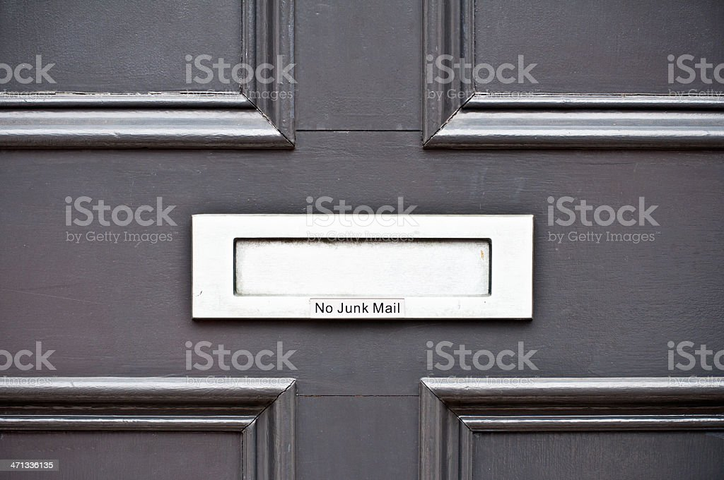 Silver slot on door with engraved text rejecting junk mail stock photo