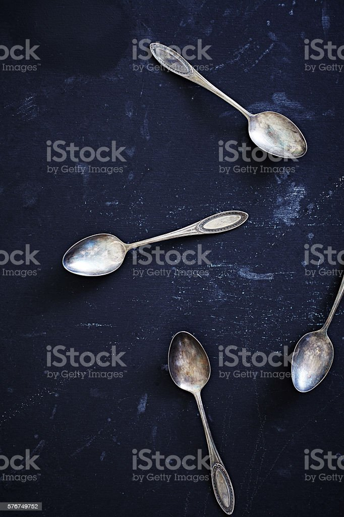 Silver spoons on dark blue texture stock photo