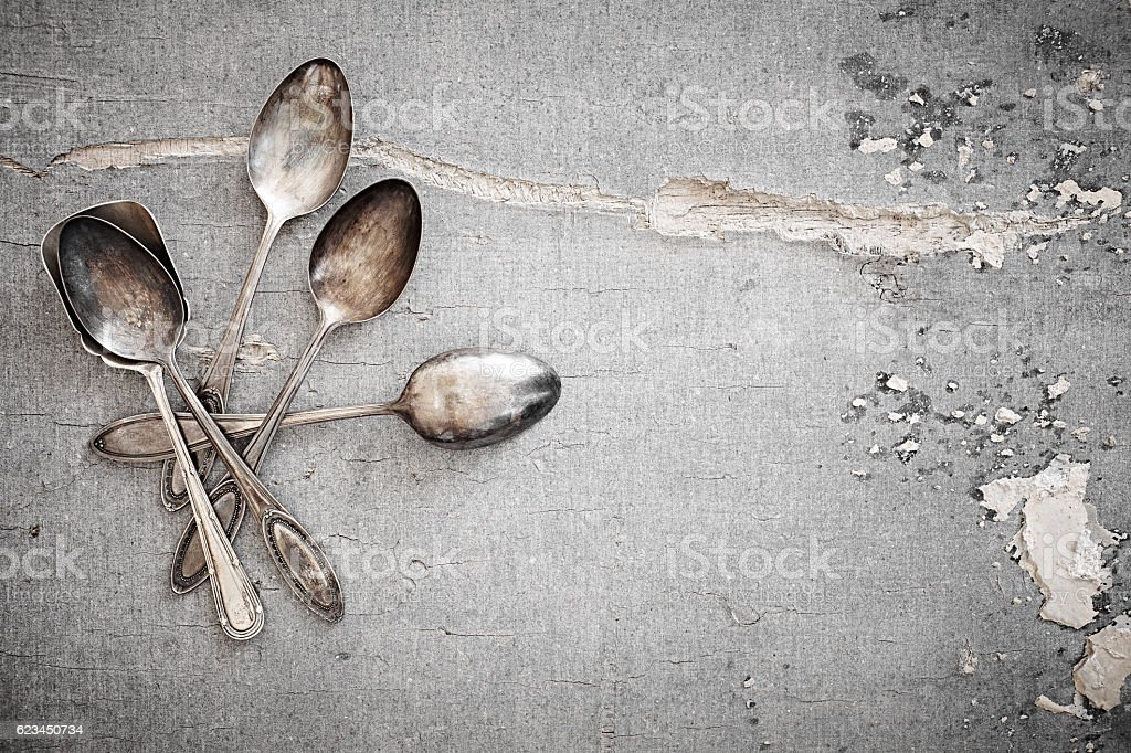 Silver spoons on old gray surface stock photo
