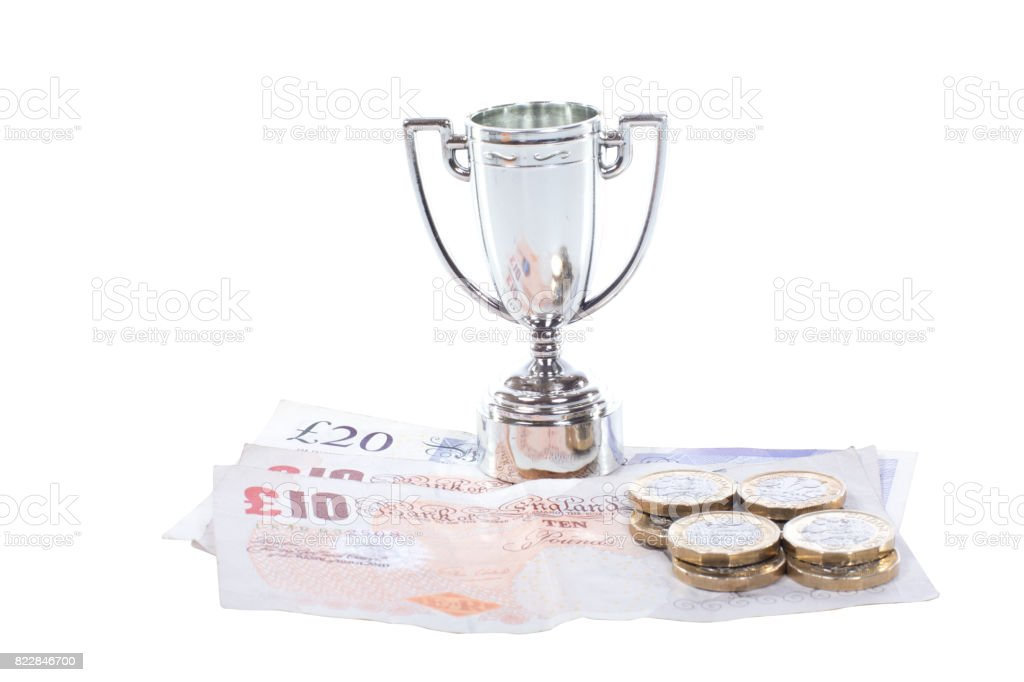 Silver sports trophy with pile of cash stock photo