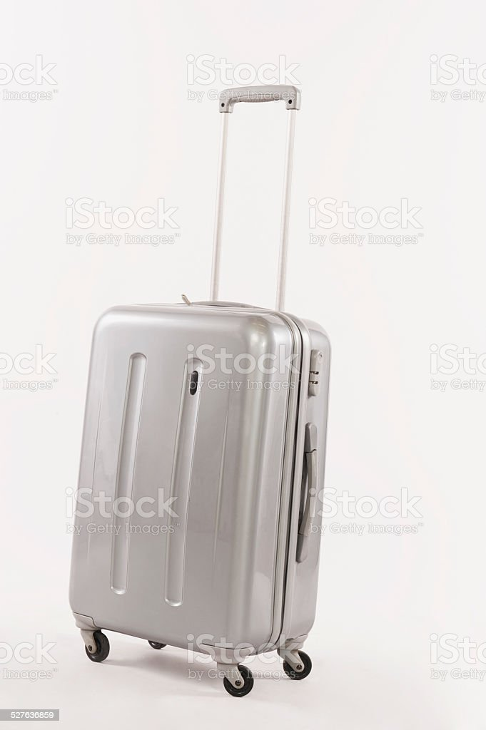 Silver suitcase with long handle against white background stock photo