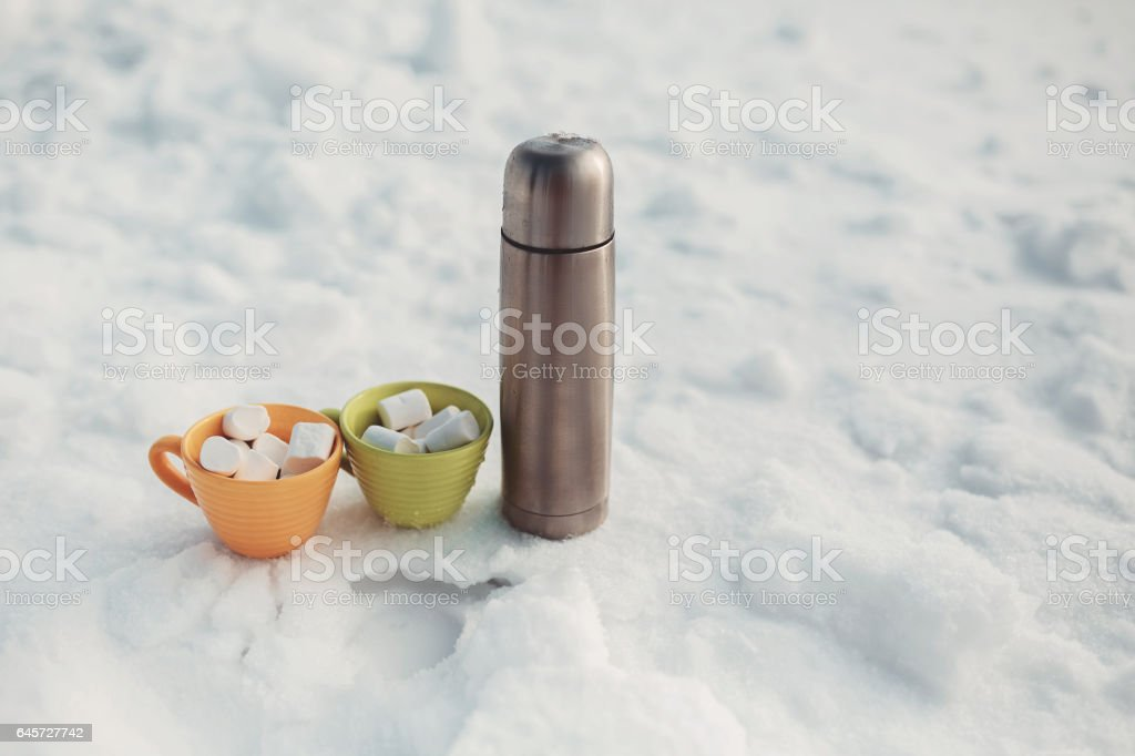 silver thermos and marshmallow in cup on snow stock photo