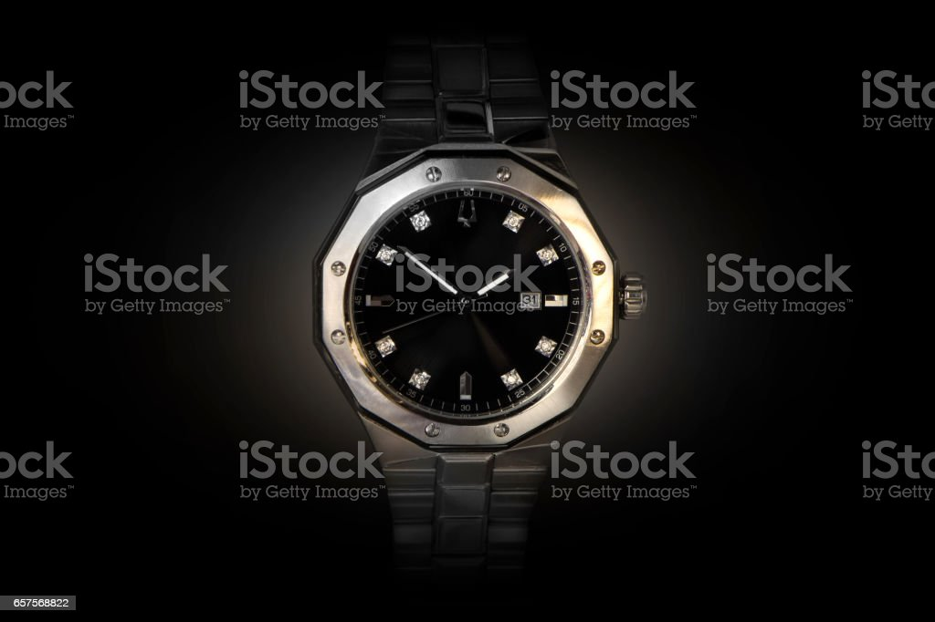 Silver watch front facing dark background stock photo