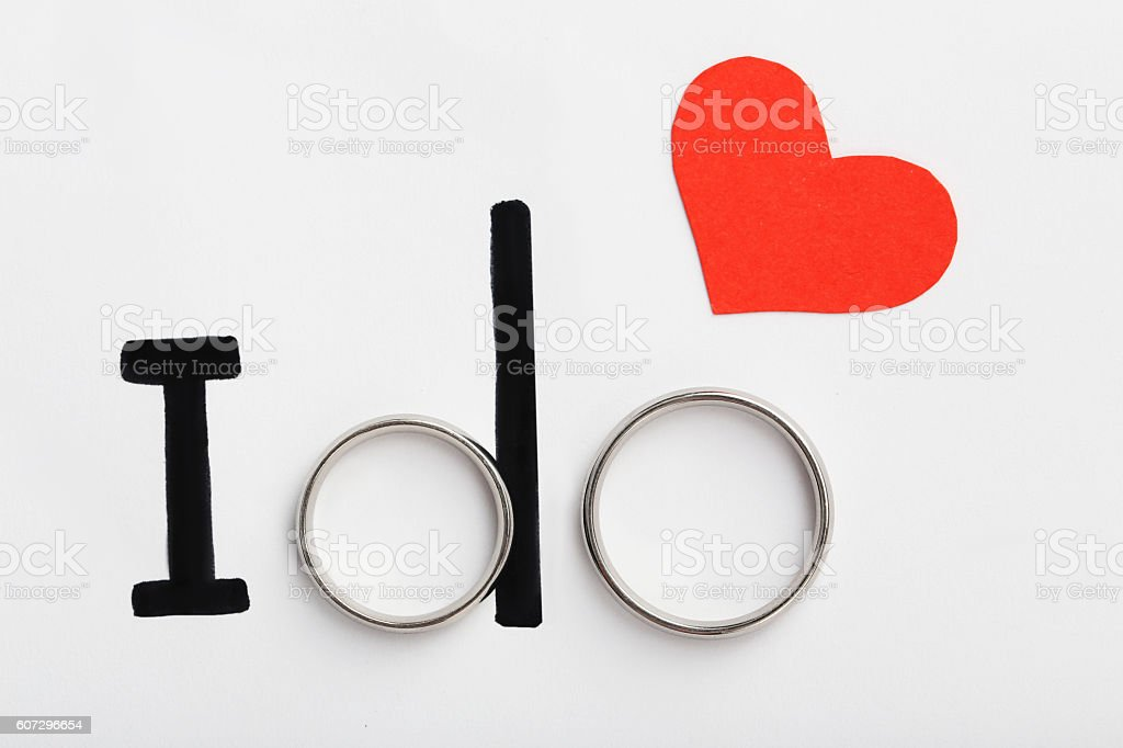 Silver wedding rings with red heart and words I do stock photo