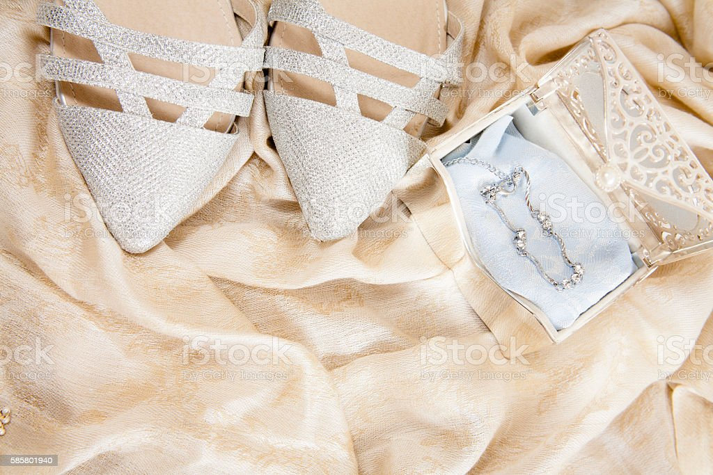 Silver wedding shoes on satin fabric with jewelry. stock photo