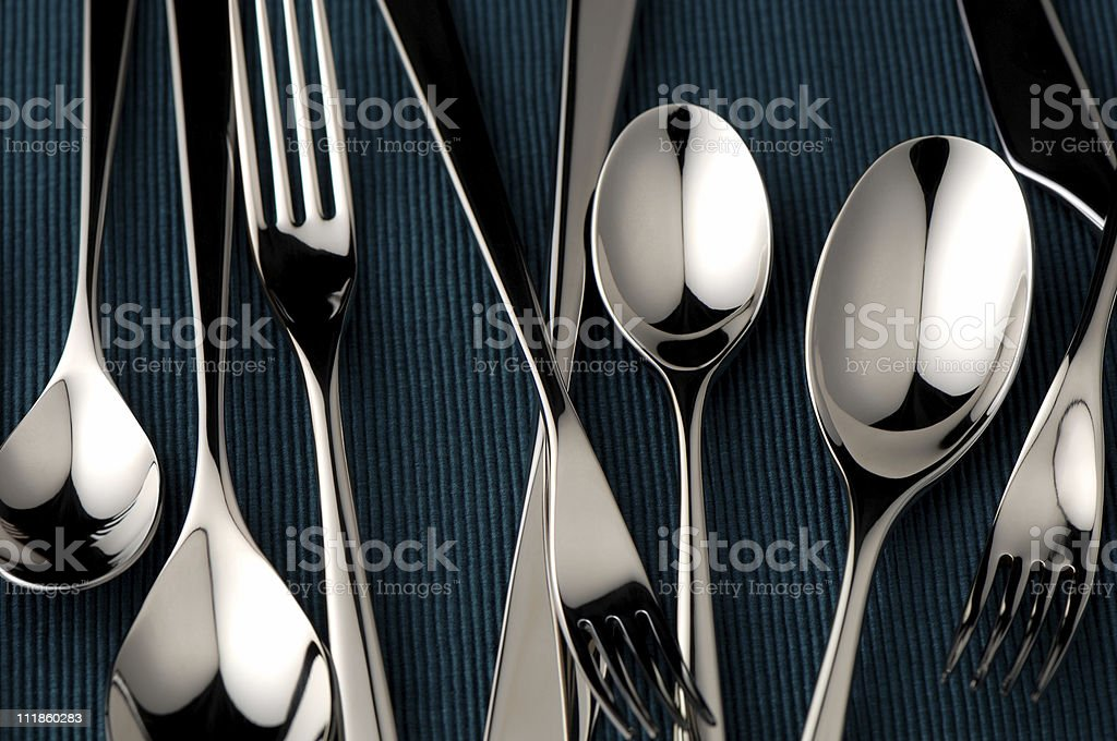 Silverware Knives Spoons Forks Randomly on Teal Background royalty-free stock photo