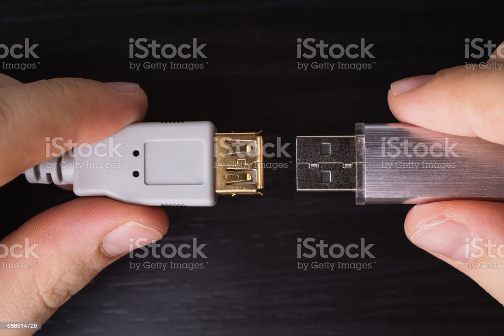 Silvery usb flash drive on a black desk and usb cable for connection close-up. A metal flash drive for storing memory in the hand on a dark background with hard light. stock photo