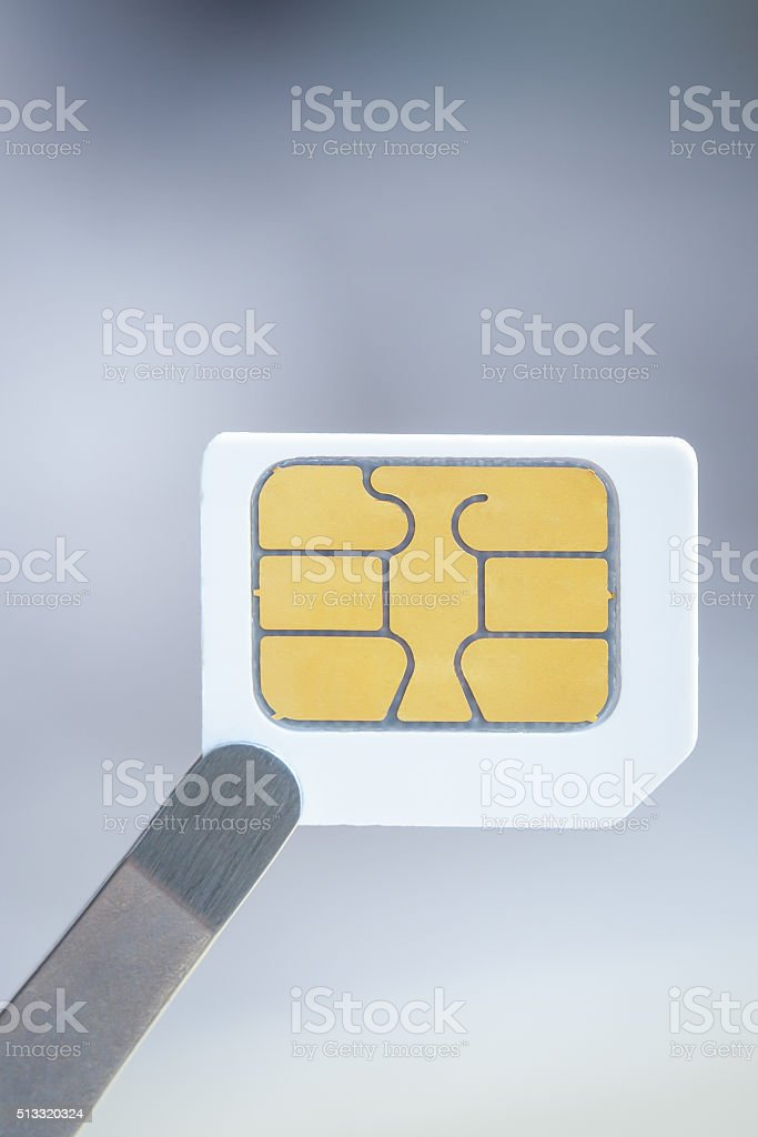 Sim card for smart mobile phone with tweezer, close up stock photo