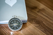 Simple compass over the book on the wooden table