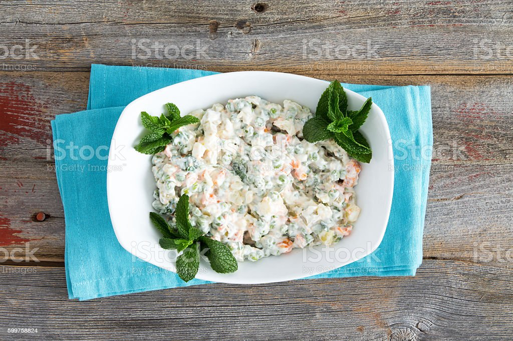 Simple Olivier Salad on old picnic table stock photo
