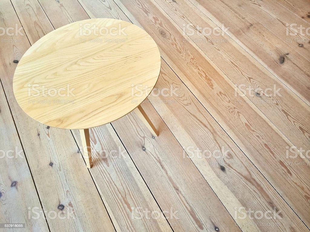 Simple round table on wooden floor stock photo