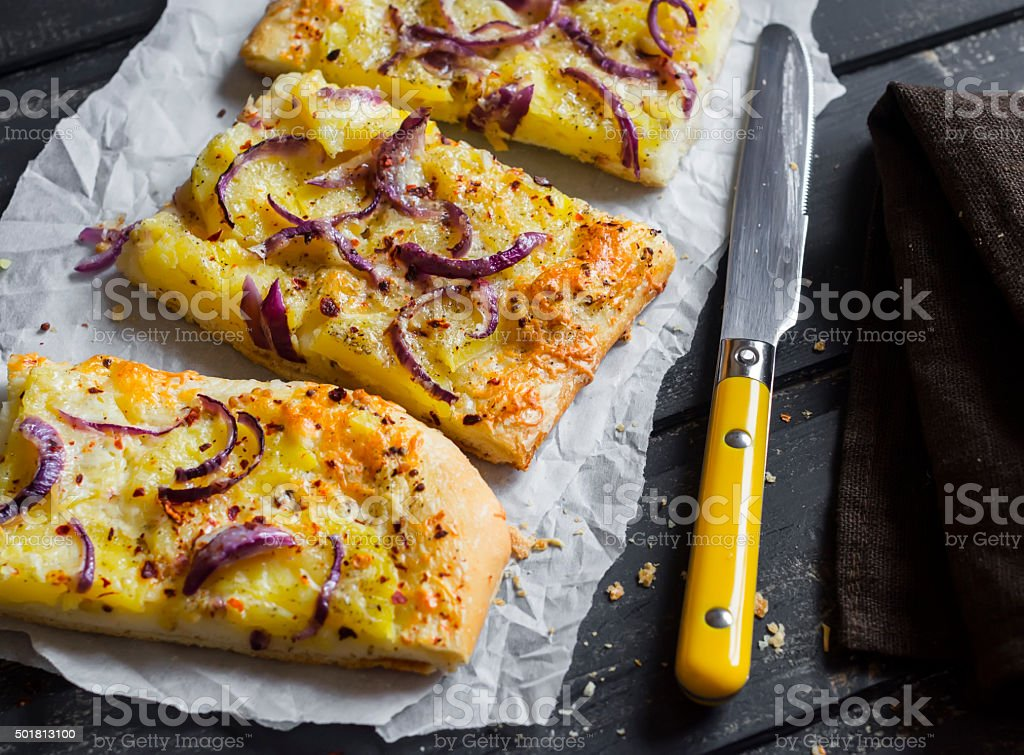 Simple rustic crispy pie with  potatoes, cheese and red onion. stock photo