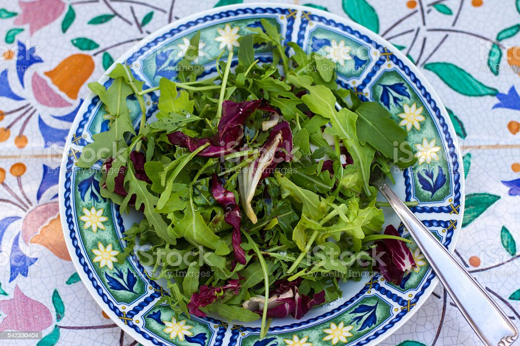 Simple Salad in Colorful Bowl on Pretty Antique Tiles stock photo