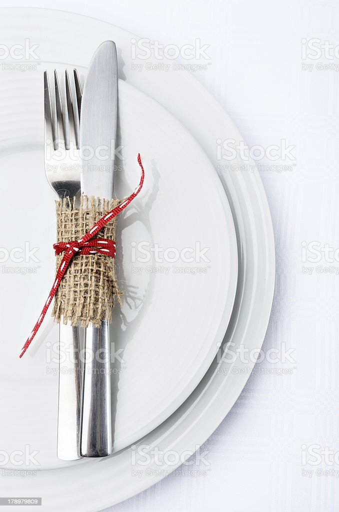 Simple table setting with white plates and silverware stock photo