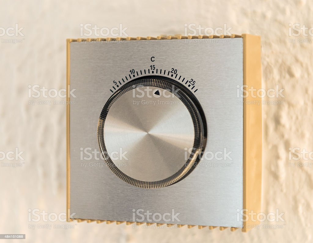 Simple traditional thermostat on interior wall stock photo