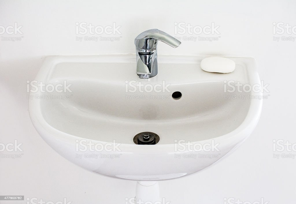 Simple white sink with a bar of soap stock photo