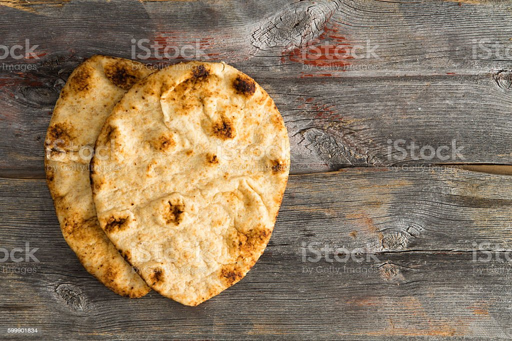 Simply delicious baked naan flatbreads on Picnic Table stock photo