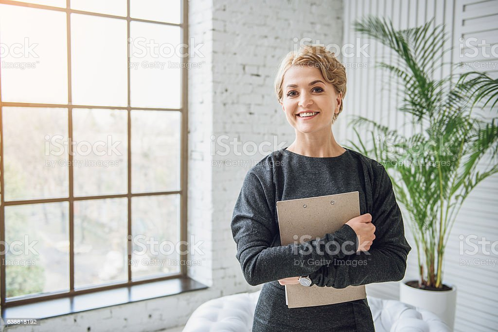 Sincerely smiling woman holding tablet stock photo