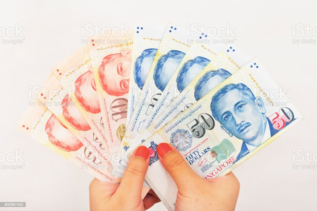Singapore currency in hand stock photo