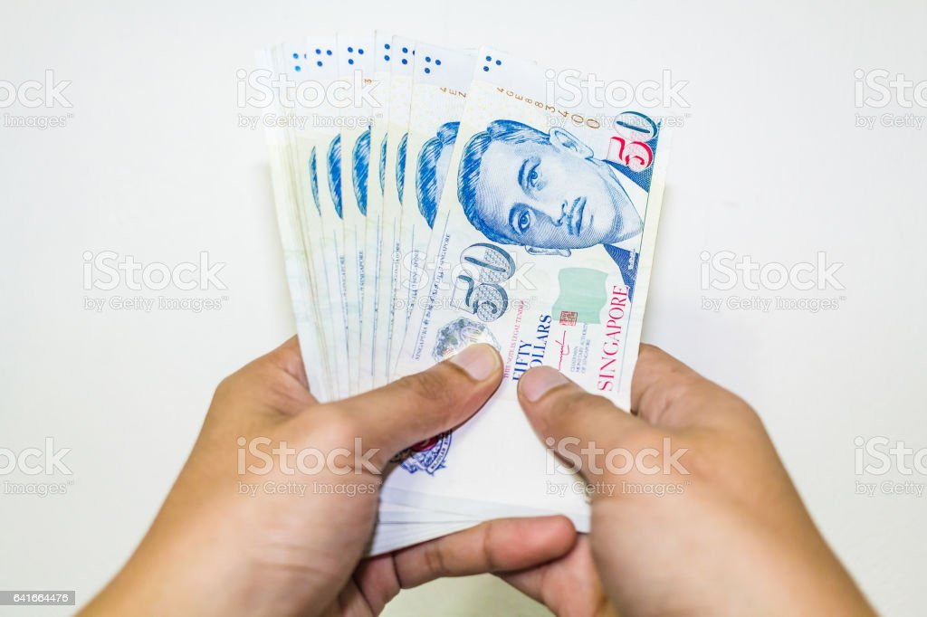 Singapore Currency with Hand Isolated in white background stock photo