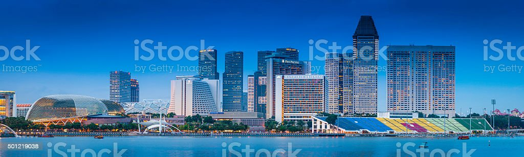 Singapore hotels and highrises illuminated at dusk beside Marina Bay stock photo