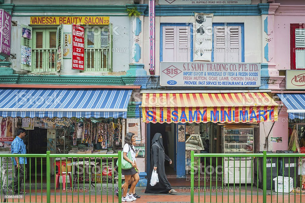 SIngapore people walking past colourful shops and shutters Little India stock photo