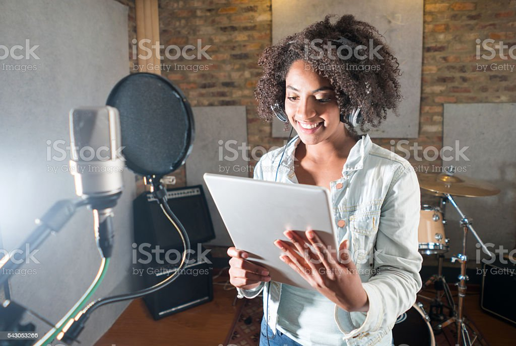 Singer at a recording studio holding a tablet computer stock photo
