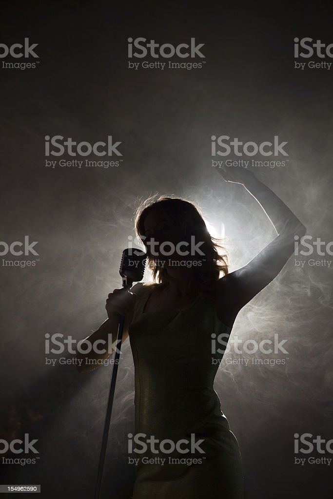 Singer backlit with arm raised stock photo