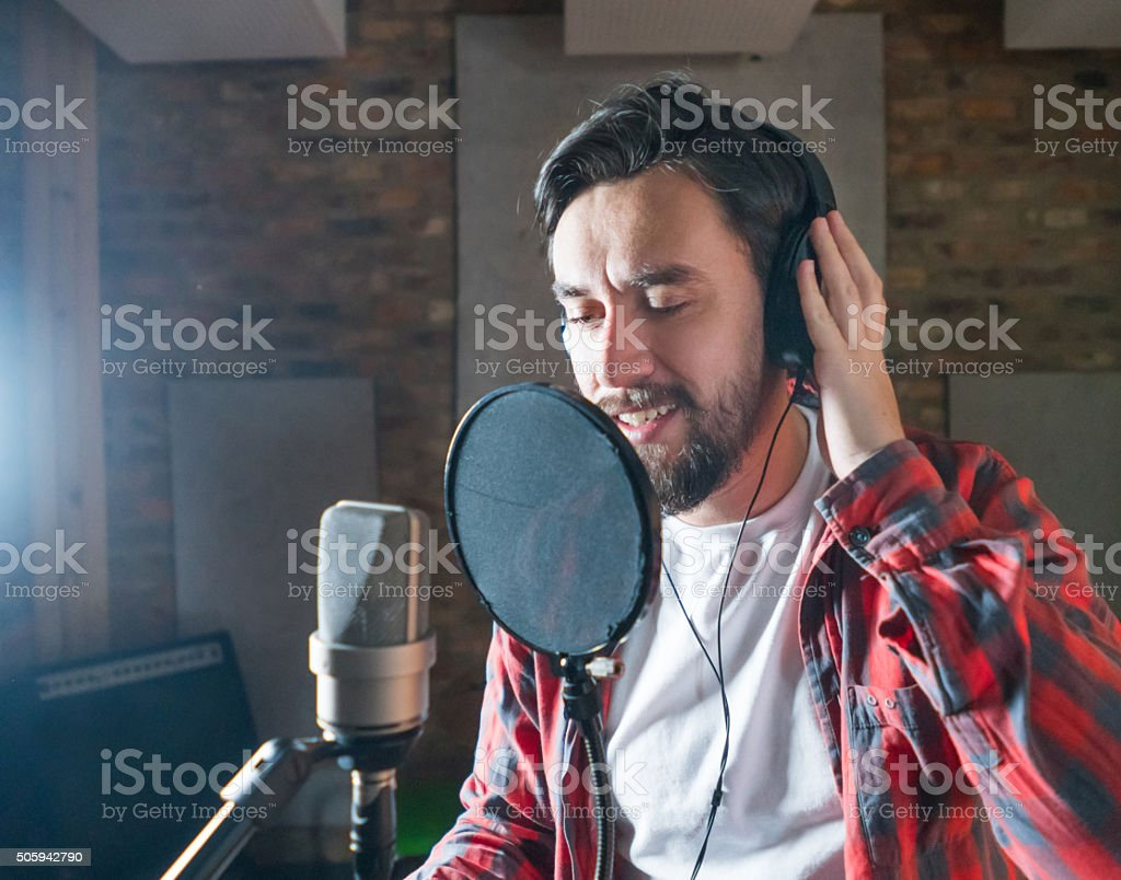 Singer singing on a microphone in a recording studio - music industry...