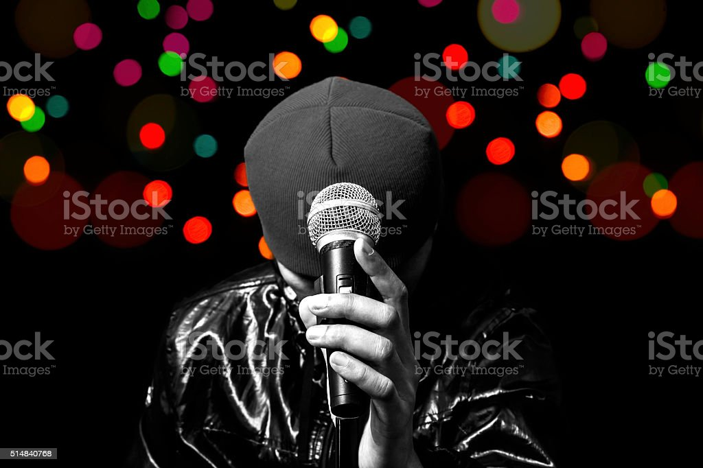BW singer left hand holding dynamic microphone with colourful light stock photo
