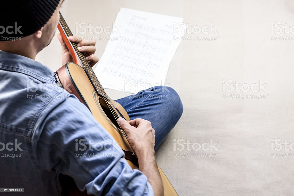 Singer songwriter plays song from sheet music tabs stock photo