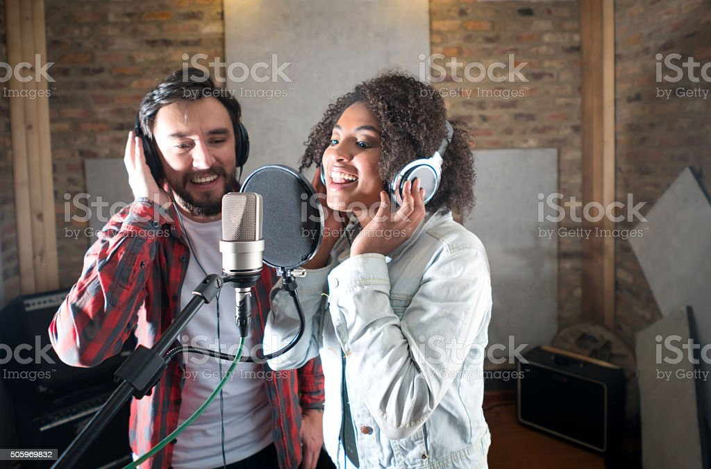 Singers singing at a recording studio stock photo