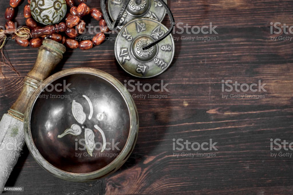 Singing a copper bowl on a brown wooden surface stock photo