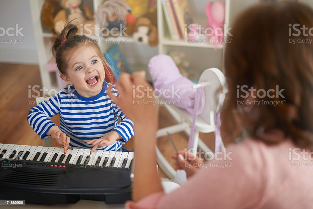 Singing and playing on musical instruments with my mommy stock photo