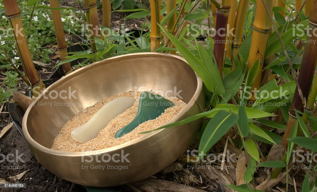 Singing bowl with sand and stones. Bamboo in the background royalty-free stock photo