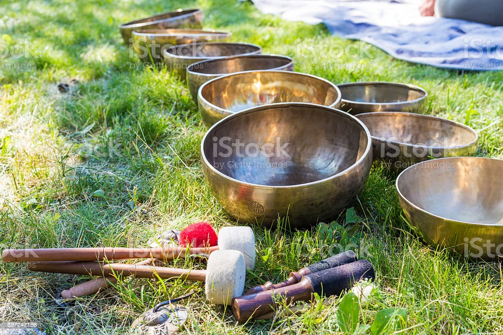 Singing bowls for massage in a row on grass stock photo