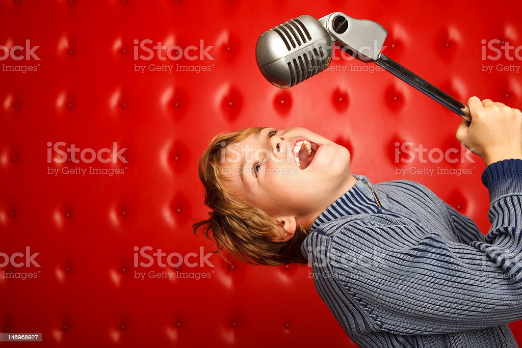 Singing boy with microphone on rack against red wall stock photo