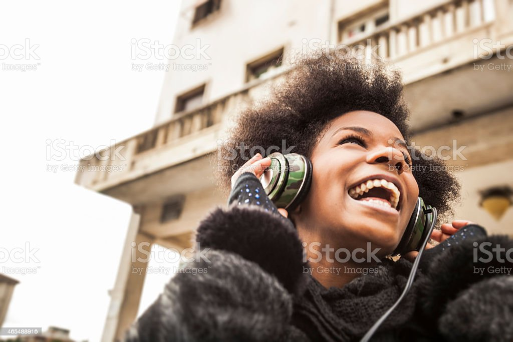Singing in the street listening to music on headphones stock photo