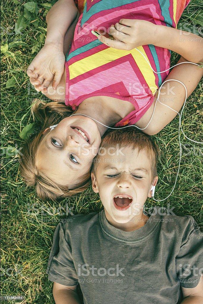 Singing Kids sharing headphones listening to MP3 Player stock photo