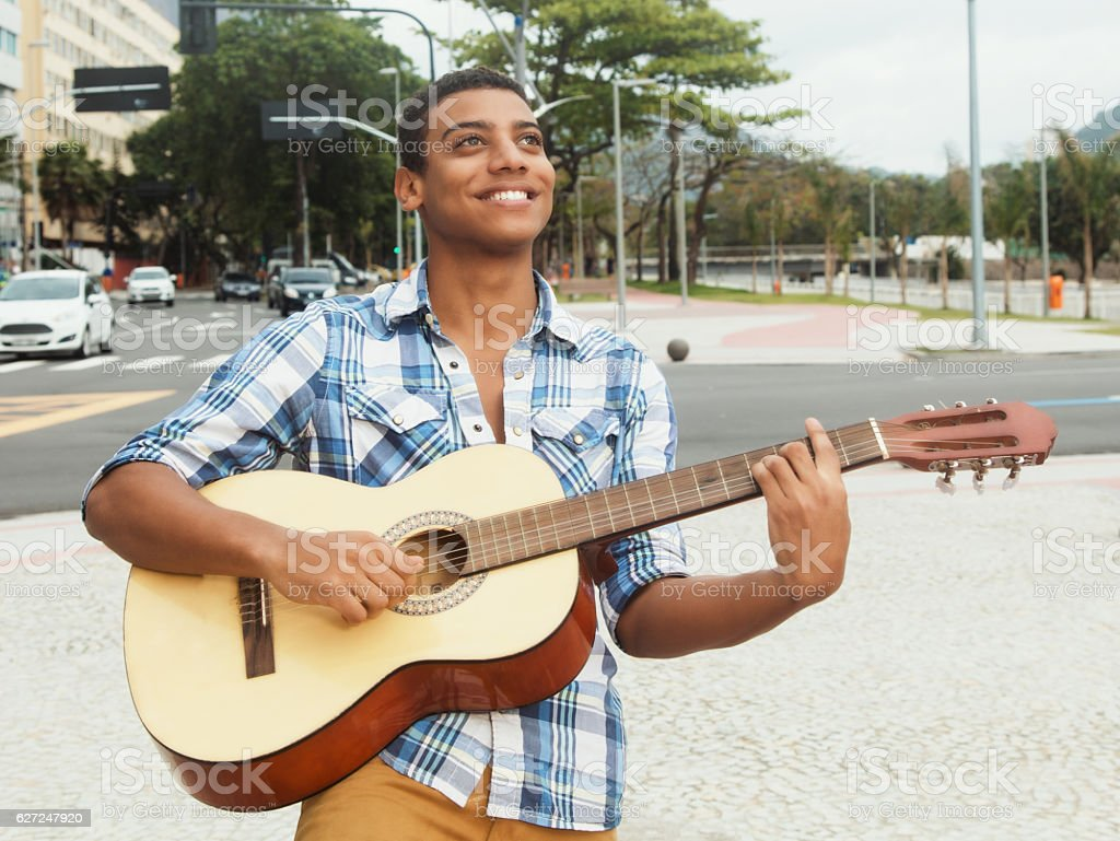 Singing street musician with guitar in the city stock photo