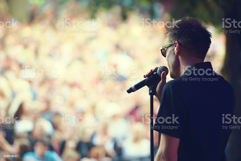 Singing to a sea of faces stock photo