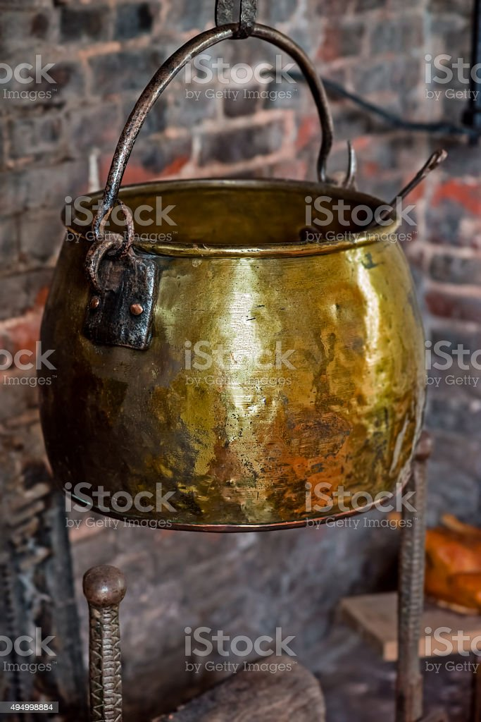 Single Antique vintage cauldron hand forged hearth fireplace old golden stock photo