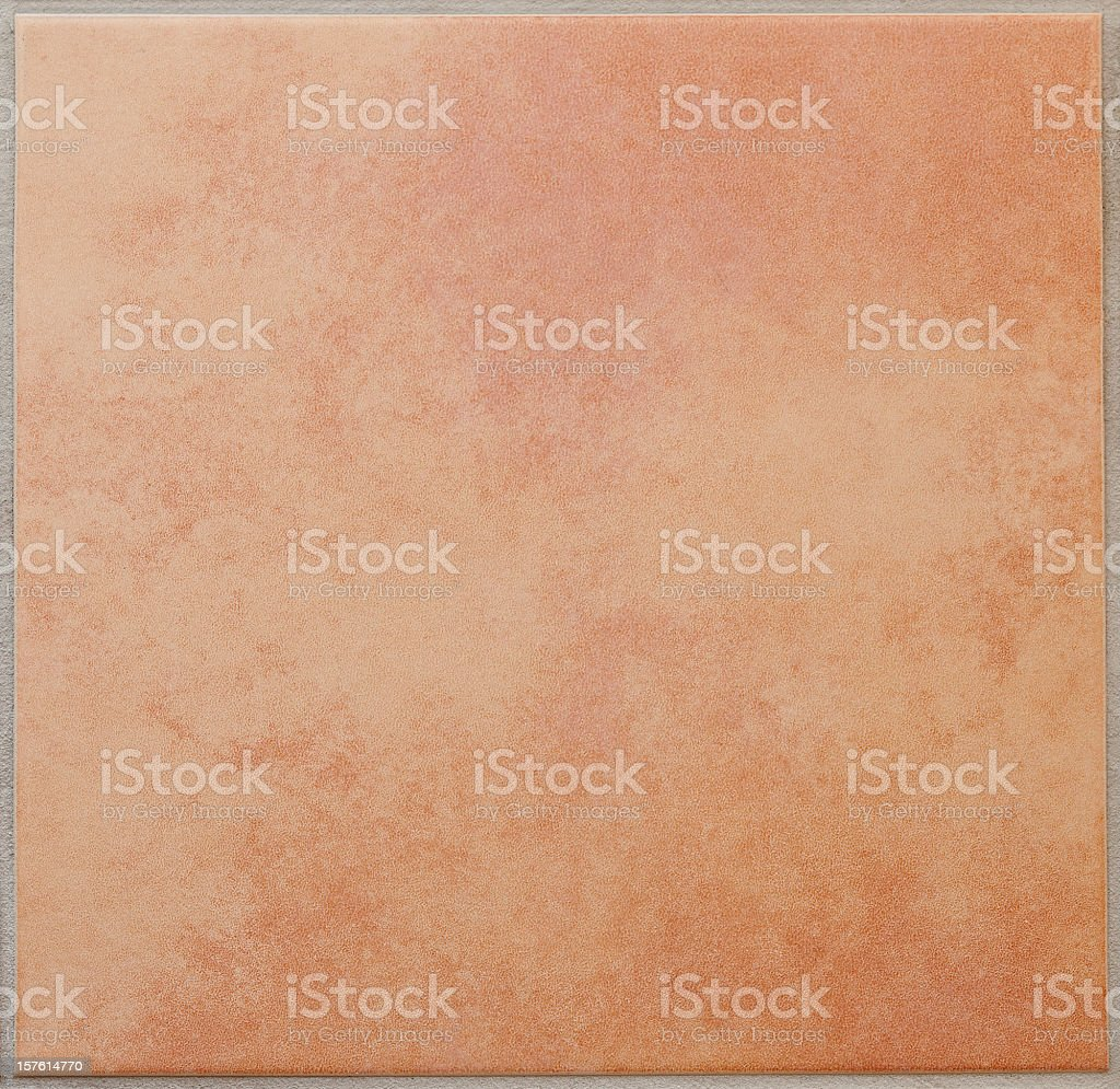 Single apricot colored ceramic tile textured full frame stock photo