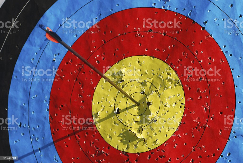Single arrow in middle of archery target stock photo