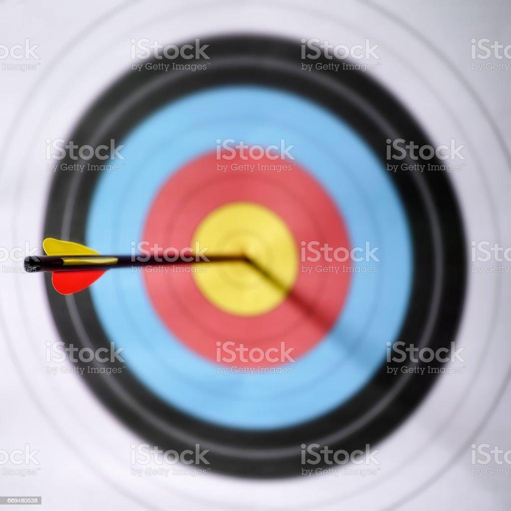 A single arrow in the bull\'s-eye of an archery target. Selective...
