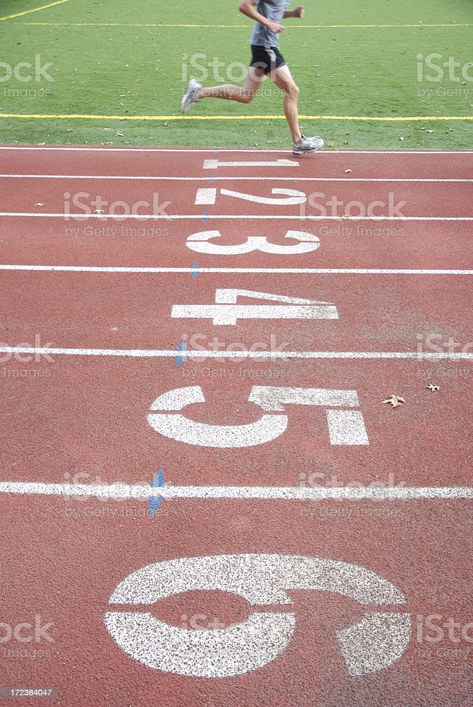 Single Athlete Runs on Number One Lane of Running Track royalty-free stock photo