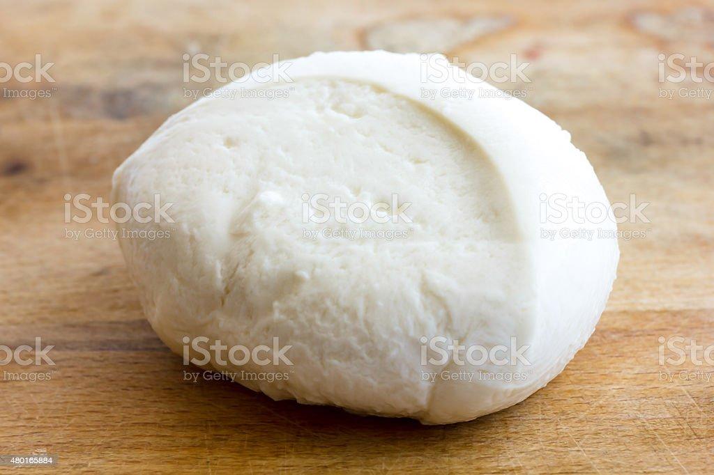 Single ball of mozzarella cheese on rustic wood surface. stock photo